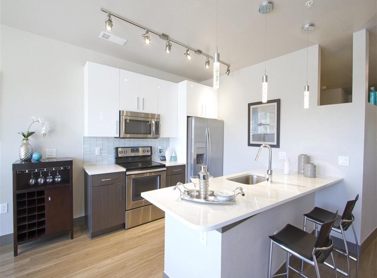 Fully equipped kitchen with stainless steel appliances, kitchen island with bar seating, and pendant lighting