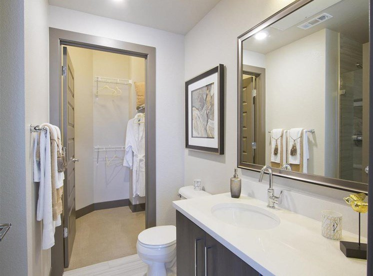 Bathroom with granite countertops, toilet, brown cabinets and bathroom decor