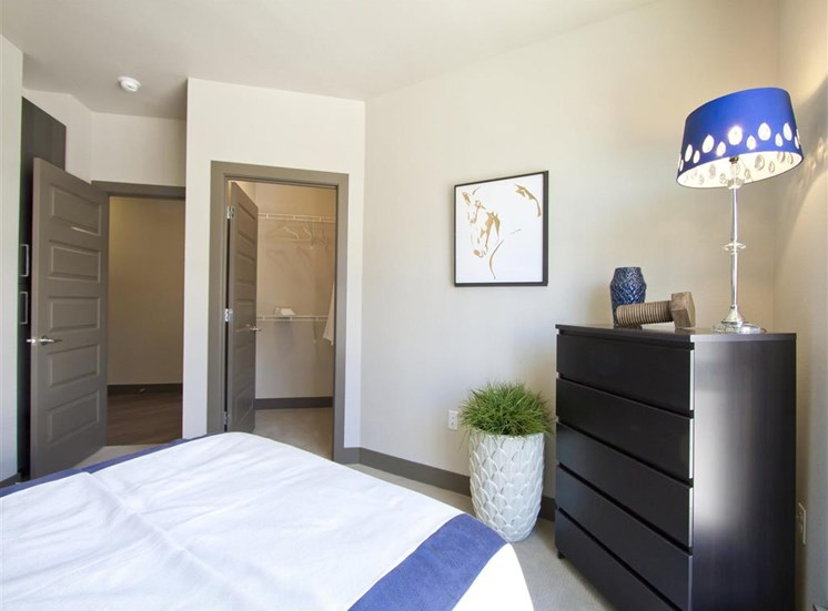 Bedroom model with large bed with white, white and blue bedding, night stand, lamp and wall decor