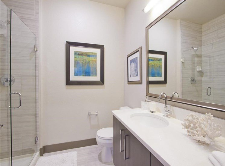 Bathroom with granite countertops, toilet, standup shower, brown cabinets and bathroom decor