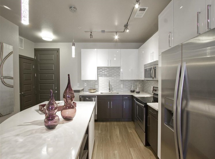 Kitchen with granite style countertops, stainless appliances, brown cabinets and decorative jars