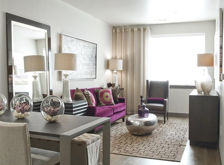 Model living room with contemporary furniture, hardwood style flooring, large window and living room decor