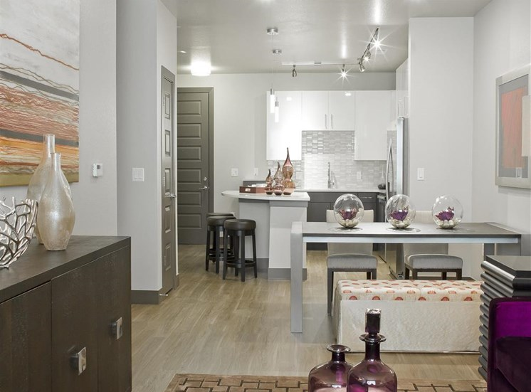 Kitchen and dining room with contemporary furniture, hardwood style flooring, brown and white cabinets, tiles backsplash, track lighting and bar.