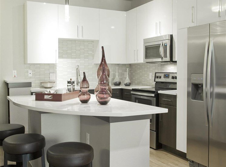 Kitchen with granite style countertops, stainless appliances, brown and white cabinets and decorative jars