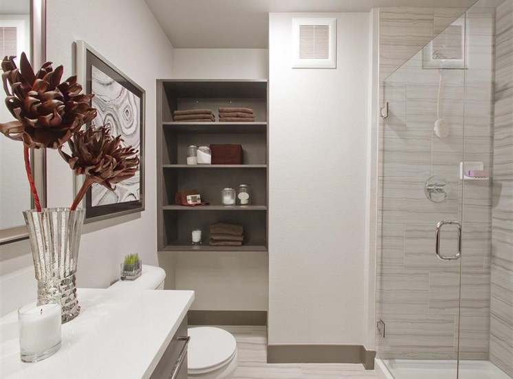 Model Bathroom with Brown Cabinets White Countertops, brown shelving and bathroom decor
