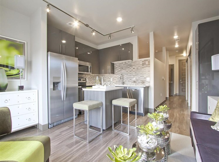 Kitchen with granite style countertops, stainless appliances, brown cabinets, island , hardwood style flooring and interior decor