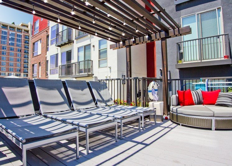 Rooftop patio with lounge chairs and large circle lounger