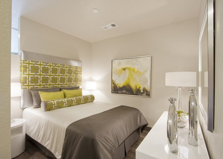 Bedroom model with large bed with white, gray and green bedding, white dresser, lamp and wall decor