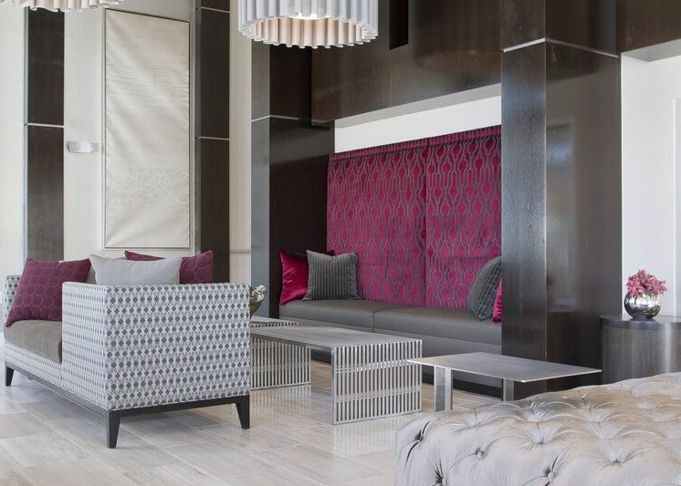 Leasing office interior waiting area with a couch, two chairs, tables and fuschia decor