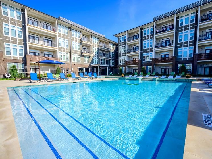 Plenty of Comfortable Lounge Chairs Surrounding Harmony Luxury Apartment's Swimming Pools