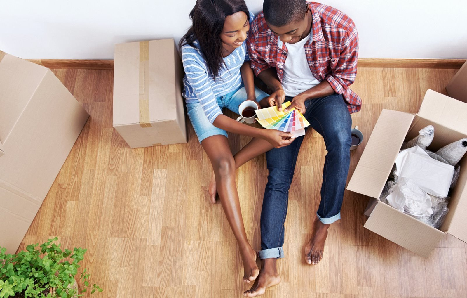 Couple sitting on the ground in their living room eating