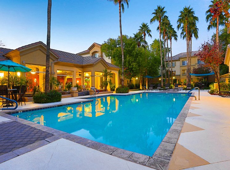 Outdoor pool with lounge seating at night