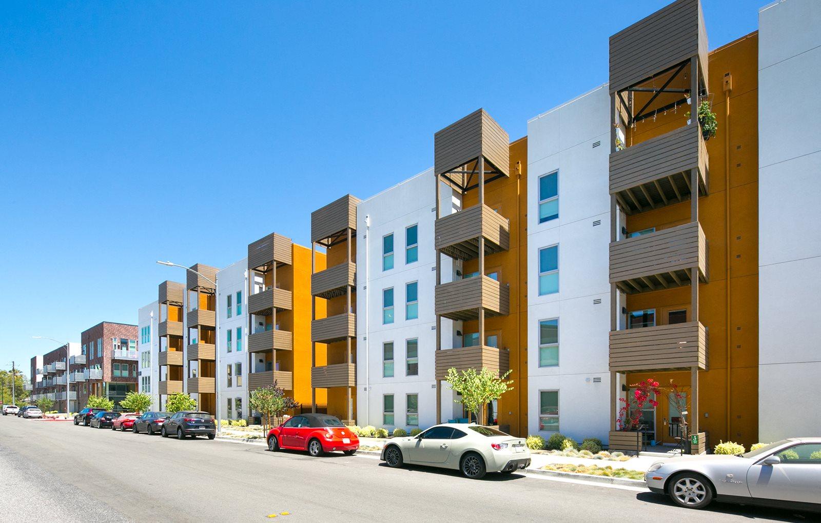 Apartments exterior white grey orange paint streetside