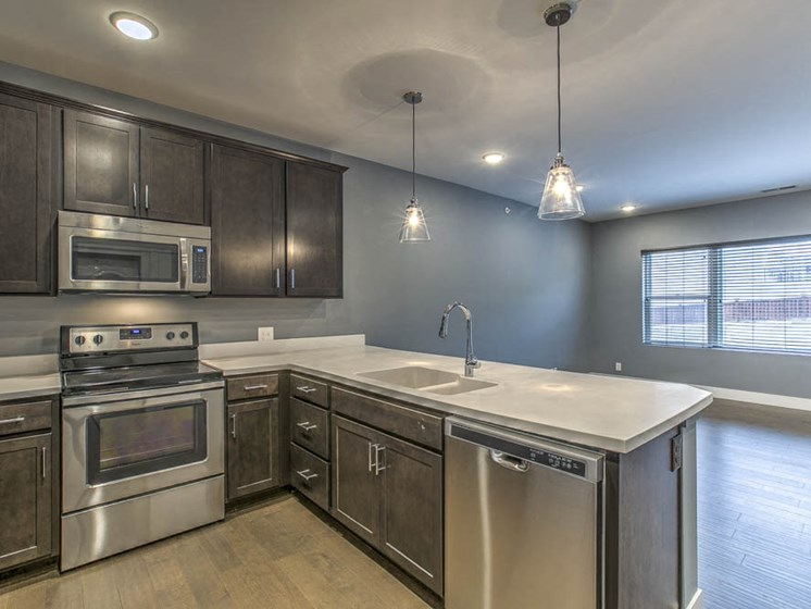 Kitchen with stainless steel appliances and dark wood cabinetry at The Helen