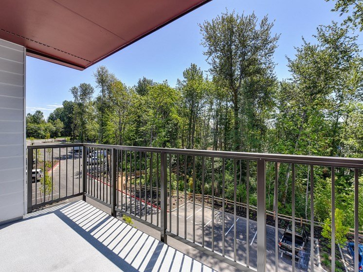 Gated Apartment Patio Exterior looking over Parking lot with Cars and Trees