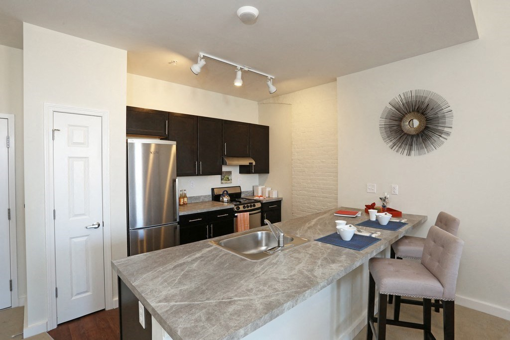 Modern kitchen features stainless steel and breakfast bar.