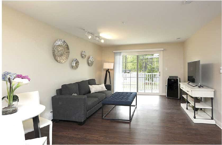 Model apartment furnished living room with wood flooring and slider
